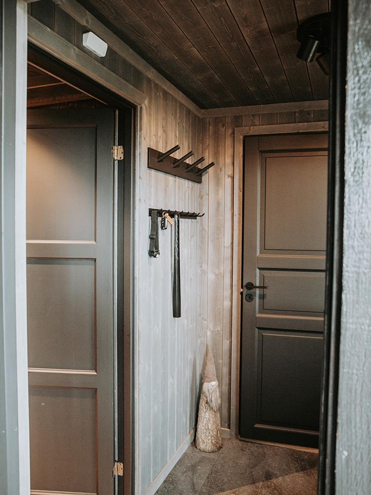 Bilde av hytte som vant hytteprisen 2021. Bilde fra gangen med Mørkne granpanel fra interiørkolleksjonen NORD.
