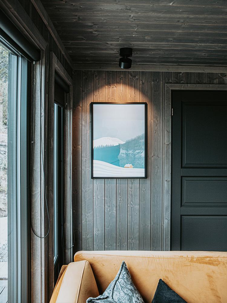 Bilde av hytte som vant hytteprisen 2021. Bilde av Mørkne granpanel i stuen fra interiørkolleksjonen NORD.